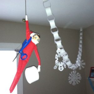 Elf on the shelf hanging from the ceiling
